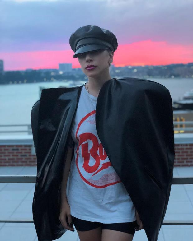 Một chiếc áo khoác da bản khủng không theo một kiểu dáng nhất định tạo nên sự cá tính đầy mới mẻ cho người mặc. Gaga chọn kết hợp cùng với một chiếc áo thu trắng và quần short ngắn đơn giản. Nhấn là là một chiếc mũ newsboy cùng chất liệu với áo khoác.