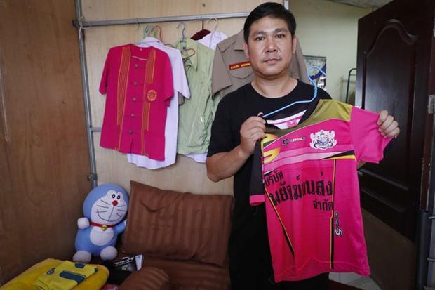 Ông Banphot Konkum và chiếc áo mà cậu bé Duangpetch thường mặc khi tập luyện. Ảnh: AP