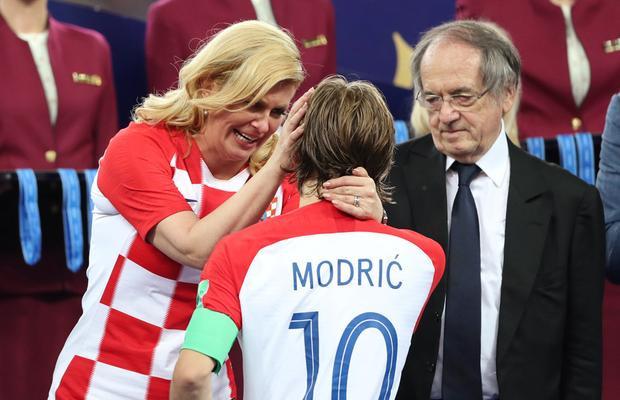 Tổng thống Kolinda Grabar-Kitarović vỗ về nỗi đau cho Modric dưới mưa. Ảnh: Reuters