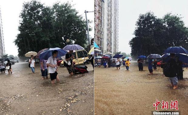 Người dân xắn quần, lội qua đoạn đường bị ngập lụt.