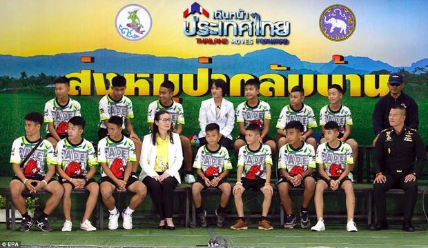 Chiều nay, 13 thầy trò đội bóng thiếu niên Lợn Hoang rời bệnh viện tới địa điểm cuộc họp báo, lần đầu tiên xuất hiện trước công chúng kể từ khi được giải cứu khỏi hang Tham Luang, miền bắc Thái Lan. Cả đội mặc đồng phục bóng đá và trông khỏe mạnhxuất hiện tại buổi họp báo trong tiếng vỗ tay chào mừng của những người có mặt tại hội trường tỉnh Chiang Rai. Các em vừa đi vào vừa làm biểu tượng cảm ơn bằng cách giơ ngón tay cái. Ảnh: EPA