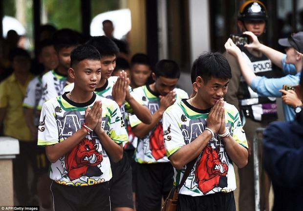 Đội bóng chào mọi người khi tới nơi ghi hình. Người phát ngôn chính phủ Thái Lan Sunsern Kaewkumnerd cho biết cuộc họp báo được tổ chức để giới truyền thông đặt câu hỏi với các em, sau đó, các thành viên đội bóng sẽ quay trở lại cuộc sống bình thường mà không bị quấy rầy. Ảnh: AFP