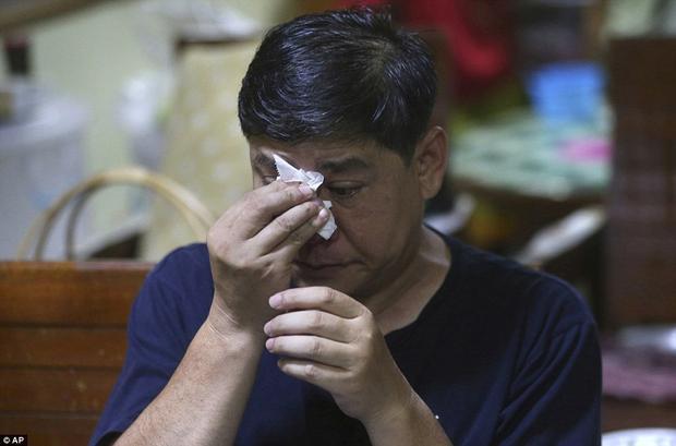 Banphot Konkum, chú của cầu thủ nhí Duangpetch Promthep, lau nước mắt khi xem cuộc họp báo qua truyền hình. Ảnh: AP