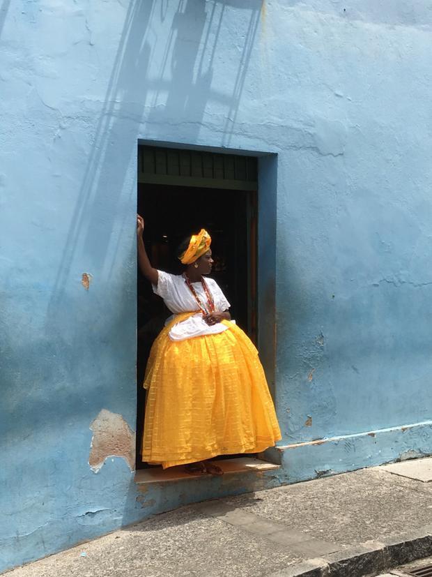 """Giải nhất Nhiếp ảnh gia của năm - """"Baiana in yellow and blue"""": Tấm hình được chụp ở Salvador de Bahia, Brazil một cách tình cờ khi chiếc xe tải dừng lại. Người phụ nữ trong trang phục Baiana truyền thống đang nhìn chiếc xe ở giờ nghỉ giải lao trong ca làm. Chụp bằng iPhone 6s. (Alexandre Weber)"""