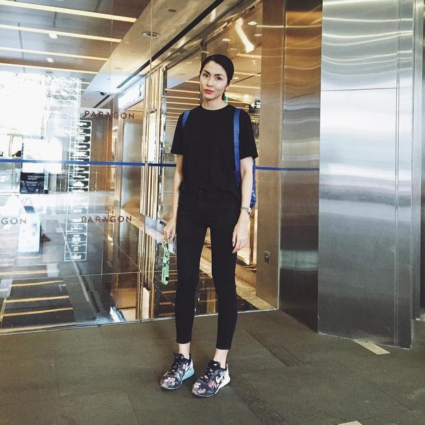 Bộ đồ đen được Hà Tăng tô đậm thêm phụ kiện là giày hoa sneaker và balo màu xanh dương đậm