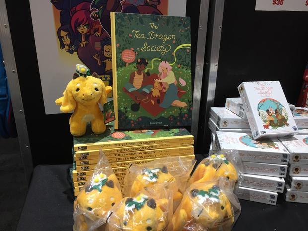 """Những chú rồng nhồi bông Chamomile bên cạnh ấn phẩm truyện tranh """"The Tea Dragon Society""""."""