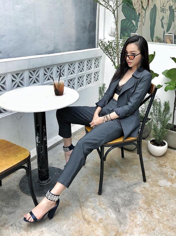Bộ suit xám kết hợp với áo lót ren trong cùng với phụ kiện là chiếc mắt kiếng màu nổi bật