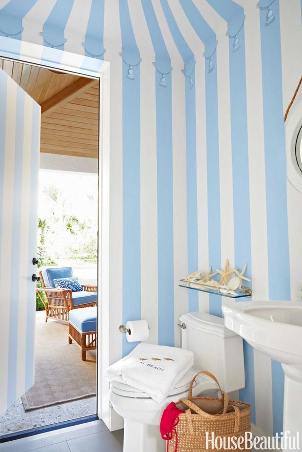 Một bức tường sọc xanh trắng giống như những chiếc lều bạt của rạp xiếc, hội chợ chính là điểm nhấn đem đến sự tươi mát cho nhà tắm này.