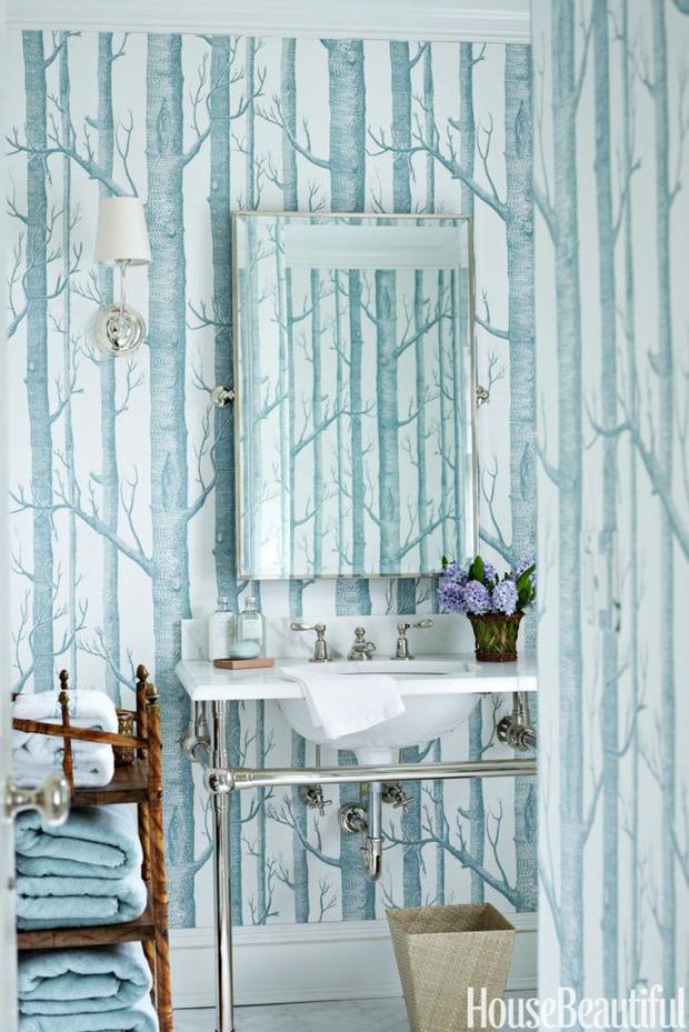 Bức tường nhà tắm màu xanh nhẹ dịu với họa tiết khu rừng không lá đem tới một không gian vừa yên bình lại cổ điển. Những vật dụng trong nhà tắm này cũng không quá cầu kì nhưng vẫn tạo được điểm nhấn.