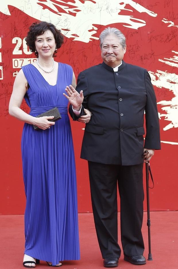 Vợ chồng Hồng Kim Bảo. Người vợ khéo léo chọn cho mình một chiếc đầm tím kết hợp với vòng cổ ngọc trai và phụ kiện là bóp đen vừa sang trọng và tinh tế.