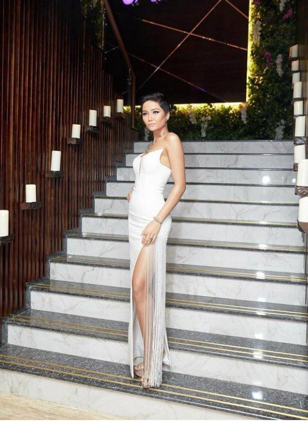 H'Hen Niê tiếp tục ghi danh mình trong danh sách sao mặc đẹp tuần với chiếc váy trắng ôm sát, xẻ cao táo bạo. Các chi tiết tua rua đính dọc bên sườn giúp mỗi bước đi của cô thêm phần mềm mại, uyển chuyển.