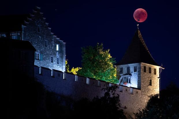 """Mặt Trăng to và đẹp """"đậu"""" trên tháp chuông của Lâu đài Laufen, Thụy Sĩ. Ảnh: EPA"""