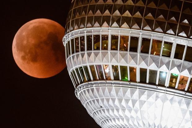 Mặt Trăng treo lơ lửng gần tháp truyền hình Berlin, Đức. Ảnh: EPA