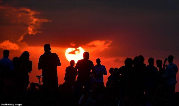 Rất đông người tập trung ở một khu vực tại Berlin, Đức để tận mắt chứng kiến hiện tượng thiên đặc biệt này. Nguyệt thực toàn phần diễn ra khi Mặt Trăng đi vào vùng tối của Trái Đất và bị che khuất hoàn toàn. Màu sắc của Mặt Trăng dần đổi sang màu đỏ thẫm. Ảnh: AFP/Getty
