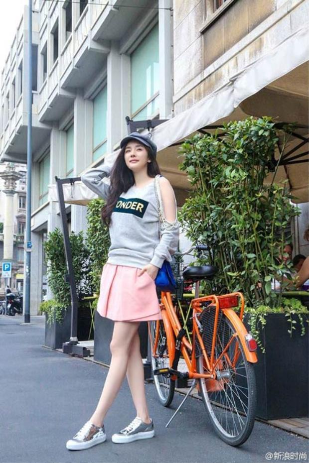 Ngọt ngào với áo nỉ hở vai phối cùng chân váy hồng và 1 chiếc flat cap cổ điển.