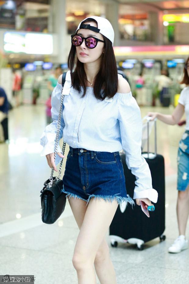 Trẻ trung, nữ tính với áo trễ vai mix cùng short jean siêu ngắn. Phụ kiện không thể thiếu của Dương Mịch ở sân bay đó chính là mắt kính và túi xách.