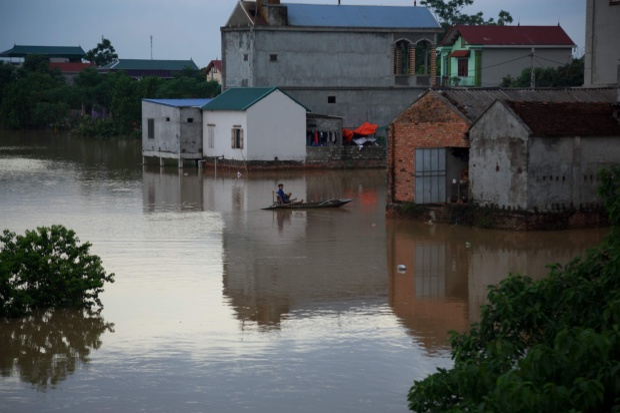 Người dân phải dùng thuyền để di chuyển sau mưa lũ.