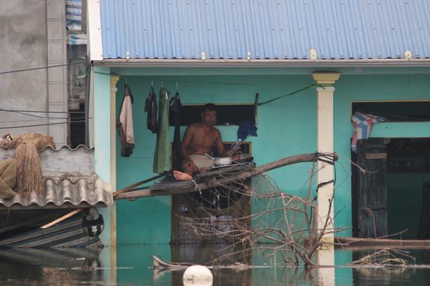 Nước ngập sâu khiến gia đình này phải ghép một số miếng ván lấy chỗ ngồi ăn uống, sinh hoạt.