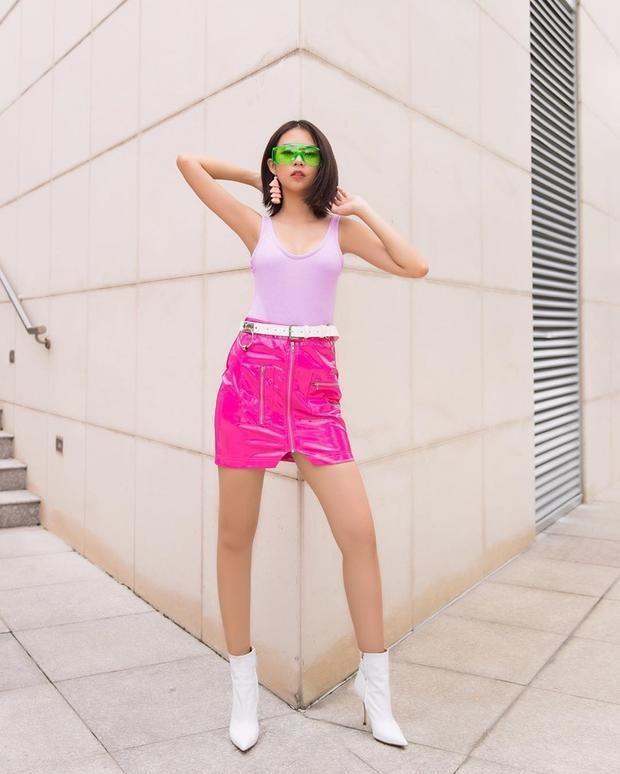 Phí Phương Anh với trang phục áo sát nách dáng ôm màu phấn, mix ấn tượng với chân váy da hồng neon cùng với phụ kiện nổi bật là chiếc mắt kiếng xanh lá cây với vóc dáng vô cùng nuột nà.