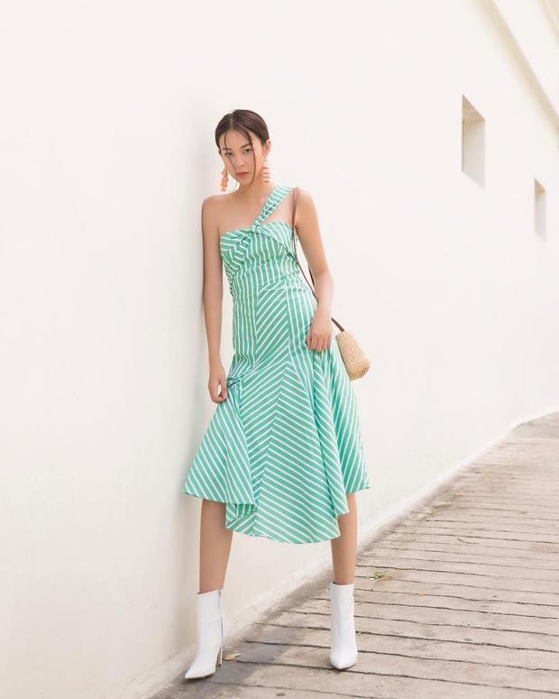 Khác hẳn với style độc đáo ở trên, cô chọn cho mình phong cách dịu dàng với chiếc đầm xanh sọc trắng kết hợp với đôi boots trắng cổ ngắn.
