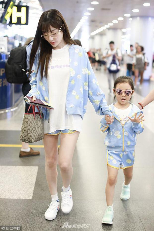 Hai mẹ con diện đồ đôi với áo phông trắng, áo khoác và quần short đồng bộ cùng với giày thể thao.