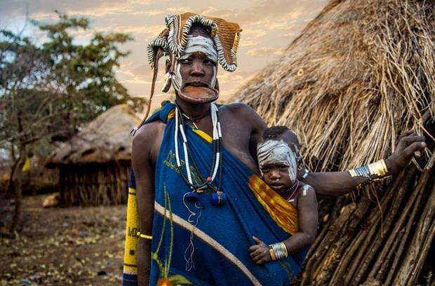 Địu con đứng trước túp lều, người phụ nữ này dù đã lồng đĩa vào môi nhưng vẫn cố gắng cười tươi để có được bức hình đẹp nhất. Tục lệ này sẽ được thực hiện với những phụ nữ đã kết hôn.