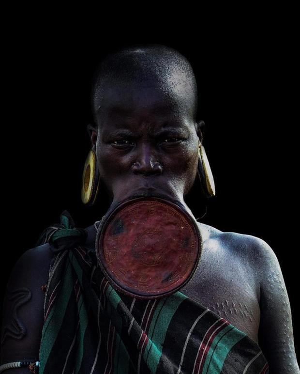 Hai răng dưới của người phụ nữ sẽ được làm gãy, sau đó họ đục một lỗi ở môi dưới và đưa một nút gỗ nhỏ vào. Nút gỗ sẽ dần thay bằng nút to hơn đến khi đủ vừa để nhét một chiếc đĩa. Kích thước chiếc đĩa có thể tăng dần theo độ tuổi của họ.