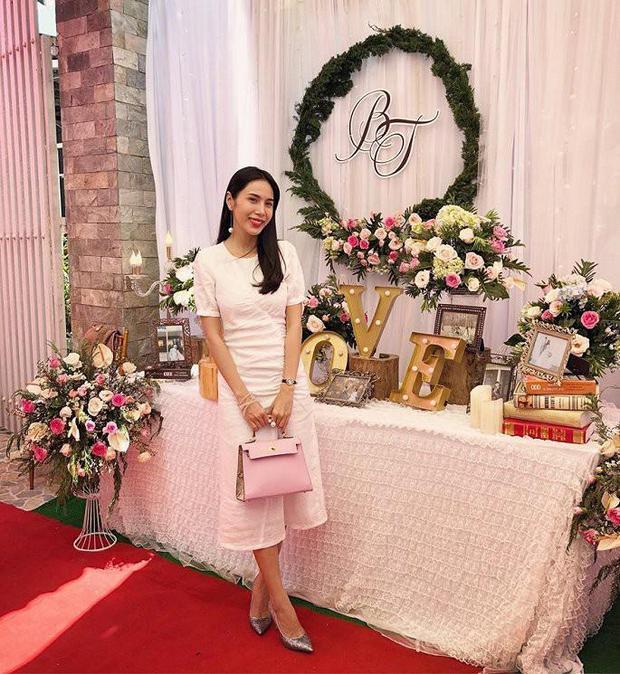 """Thủy Tiên cũng lựa chọn chiếc váy này khi tham dự đám cưới của Fans. Giọng ca """"Giấc mơ tuyết trắng"""" sử dụng túi xách Hermes, giày cao gót ánh kim làm điểm nhấn."""