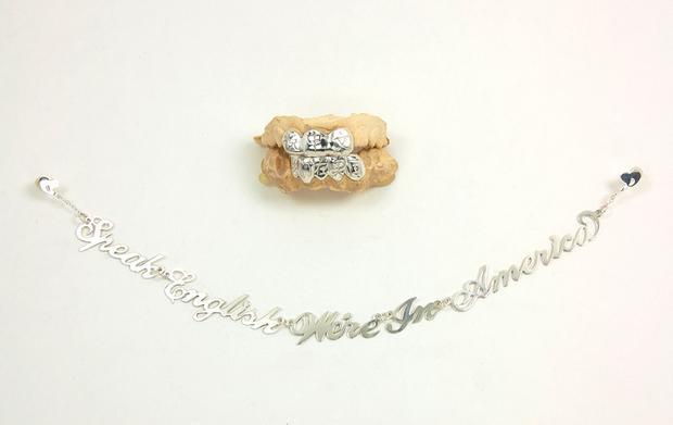 """Hoa tai liền với dòng chữ """"Speak English we're in America"""" đi kèm với món trang sức được cài lên răng khắc tiếng Hoa"""