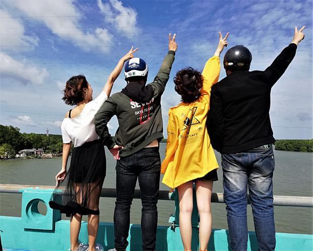 Một nhóm bạn tạm dừng tại một cây cầu ven đường đi để check - in