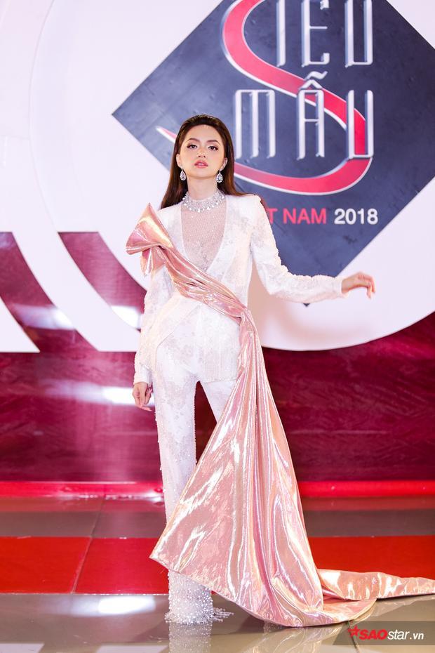 Bộ suit trắng đính kết cầu kỳ của nhà thiết kế Đỗ Long được cô nàng mix cao tay với áo see thought bên trong làm tăng sự gợi cảm quyến rũ.