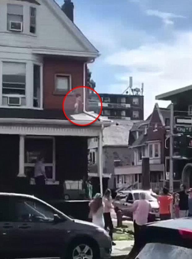 Đứa bé mắc kẹt trên mái nhà tầng 2.