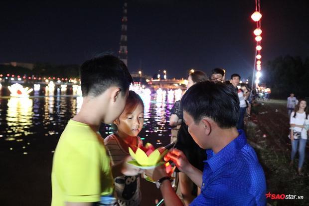Gia đình cùng nhau thắp nến cho hoa đăng để thả xuống nước
