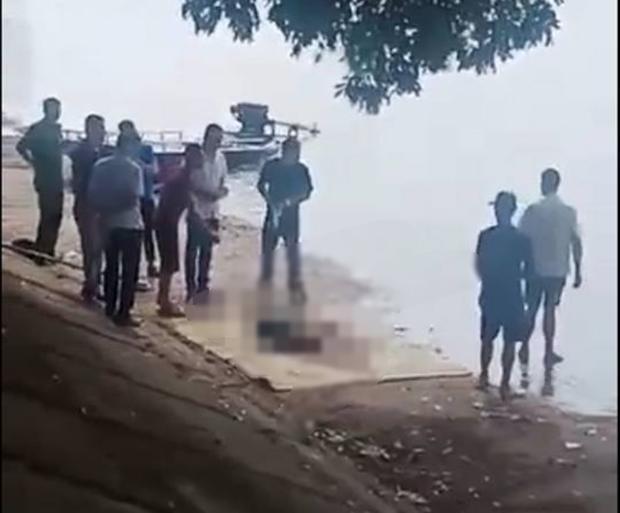 Lực lượng chức năng đưa thi thể nạn nhân lên bờ.
