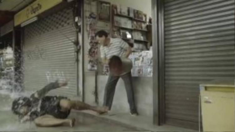Người chủ tiệm luôn tìm cách đuổi anh chàng vô gia cư đi cho khuất mắt mình. (Ảnh chụp từ clip)