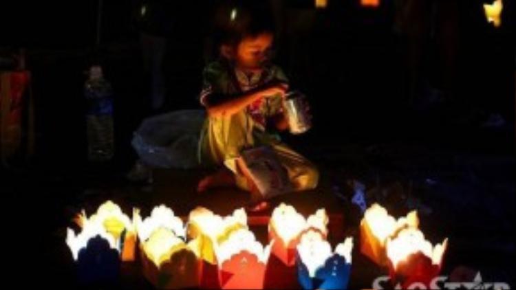 Những em bé mặc trang phục truyền thống độc đáo bên hoa đăng, thu hút được nhiều sự chú ý của du khách.