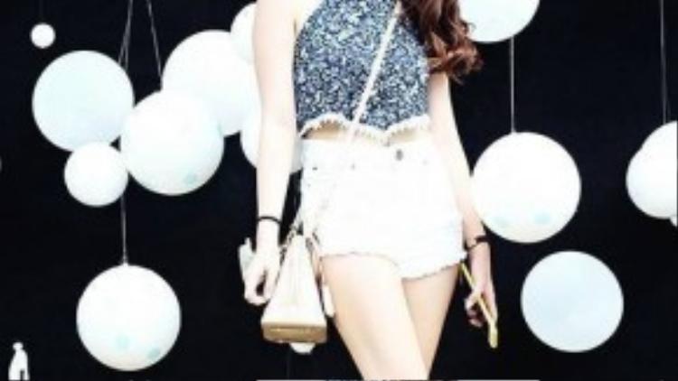 Áo yếm crop-top mix cùng short jeans trắng không chỉ giúp Lý Phụng khoe khéo làn da trắng nõn nà mà còn làm tôn lên vóc dáng chuẩn của mình. Chiếc túi mini vừa là phụ kiện để mua sắm, vừa là điểm nhấn bổ sung cho set đồ hoàn hảo của cô nàng.