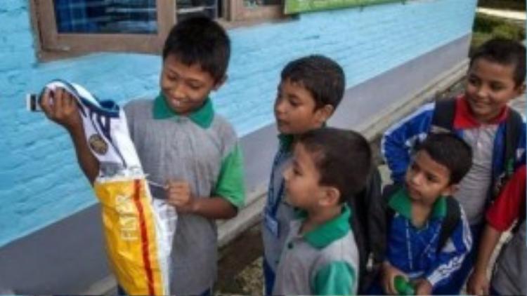 Cậu nhóc mở ngay gói quà trước ánh mắt ngưỡng mộ của bạn bè.