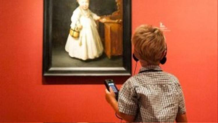 Một bé trai đang sử dụng thiết bị audio guide khi chiêm ngưỡng một tác phẩm hội họa