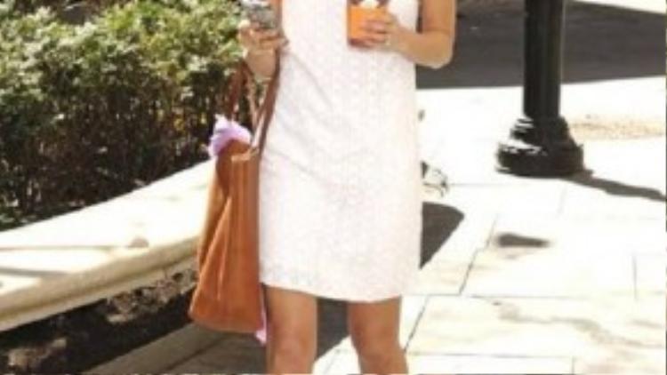 Màu trắng chưa bao giờ là lỗi mốt. Chiếc váy được kết hợp với túi xách da và sandals quai mảnh tạo sự thoải mái nhưng cũng không kém sành điệu.