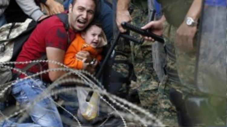 Một người đàn ông và cậu bé bị kẹt giữa cảnh sát chống bạo động Macedonia và di dân trong một cuộc đụng độ gần ga xe lửa biên giới của thành phố Idomeni, miền bắc Hy Lạp, hôm 21/8.