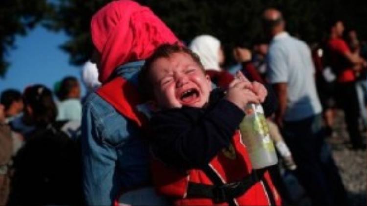 Em bé Syria khóc trên lưng mẹ khi hai mẹ con đang đợi tàu ở thành phố Idomeni, Hy Lạp. Từ đây, người di cư sẽ tiếp tục tiến về hướng bắc để tới Macedonia.