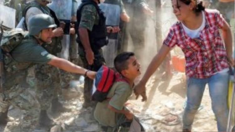Cảnh tượng quân đôi trấn áp những người di cư tại biên giới Macedonia.