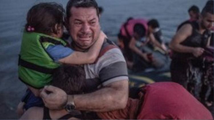 Một người cha ôm gia đình khóc trong vui mừng vì tất cả đã an toàn đến được đảo Kos.