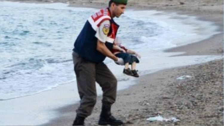 Cảnh sát bên cạnh thi thể Aylan Kurdi, 3 tuổi, cư dân người Kurd trên một bãi biển ở Thổ Nhĩ Kỳ. Kurdi cùng mẹ và anh trai thiệt mạng trong hành trình trốn khỏi cuộc chiến ở Syria. Bức ảnh được chia sẻ trên mạng xã hội và khiến nhiều người xúc động.