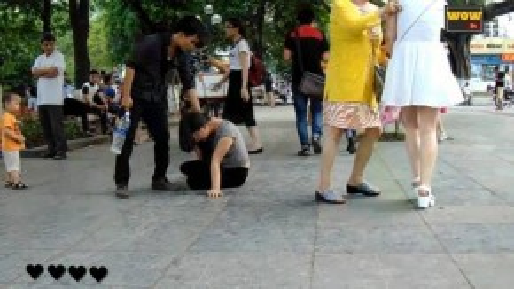 Cô gái (mặc đầm trắng), góc bên phải có ý định vào can ngăn, nhưng ngay lập tức bị người phụ nữ đi cùng (áo khoác vàng) cản lại. (Ảnh chụp từ clip)
