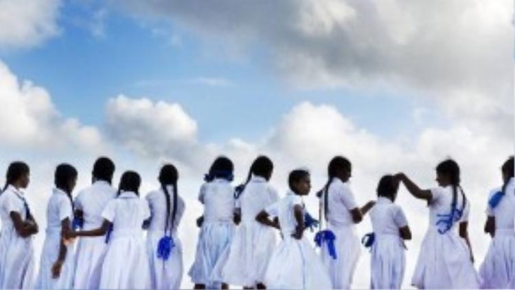 Dải ruy băng xanh colbat thắt ở đuôi bím tóc nổi bật trên bộ đồng phục đầm midi trắng của nữ sinh ở Sri Lanka.