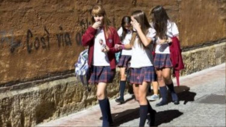 Nữ sinh Tây Ban Nha nổi bật trong những chiếc váy xếp li họa tiết kẻ sọc cổ điển, áo polo cùng tất cổ cao.