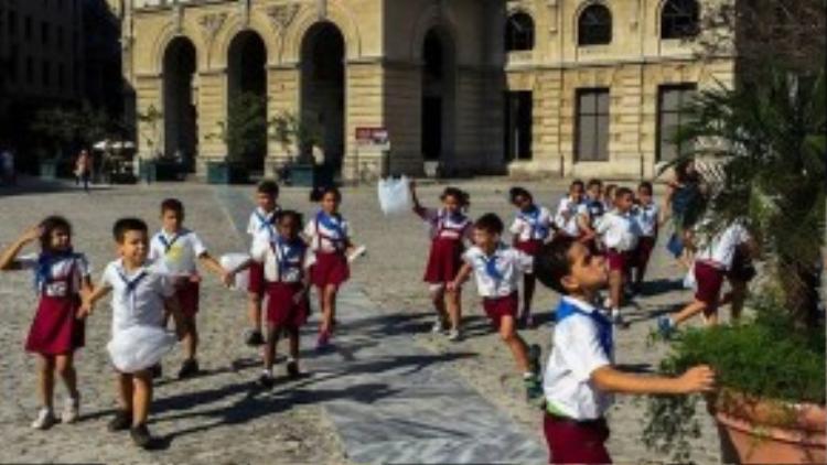 Học sinh Cu Ba năng động trong bộ đồng phục quần short hoặc váy lửng, điểm nhấn là chiếc khăn choàng màu xanh trên cổ áo.