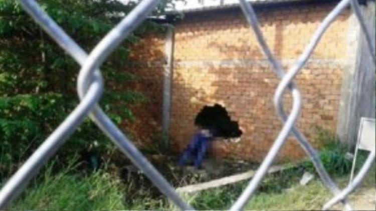 Thi thể một trong hai thanh niên nằm ngang lỗ thủng của nhà kho. Ảnh: T.D.